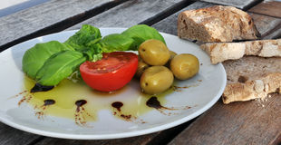 Olijfolie, basilicum, tomaat, olijven en brood Royalty-vrije Stock Afbeeldingen