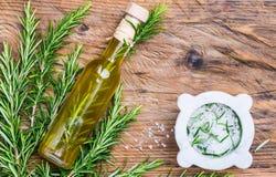 Olijfolie die met rozemarijnkruid en aromatisch zout wordt gegoten royalty-vrije stock afbeeldingen