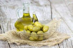 Olijfolie en groene olijven Stock Foto