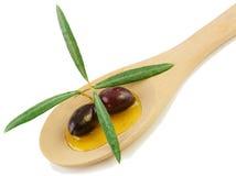 Olijfolie en verse olijven in een houten lepel Royalty-vrije Stock Afbeeldingen
