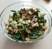 Olijfolie het gieten in kom salade royalty-vrije stock afbeelding