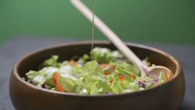 Olijfolie het gieten over gemengde salade stock video