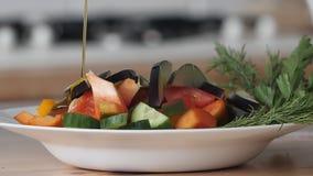 Olijfolie het gieten over gemengde salade Olijfolie het gieten over gemengde salade stock footage