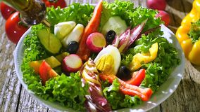Olijfolie het gieten over gemengde salade stock videobeelden