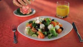 Olijfolie het gieten over gemengde salade op de witte plaat stock videobeelden