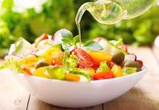 Olijfolie het gieten over plantaardige salade Stock Afbeeldingen
