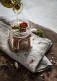 Olijfolie in kruik met droge tomaten wordt gegoten die Stock Foto's