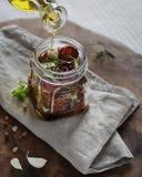 Olijfolie in kruik met droge tomaten wordt gegoten die Stock Foto