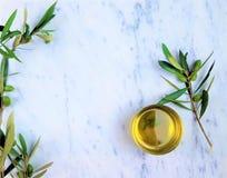Olijfolie met een tak van groene olijven op marmeren achtergrond royalty-vrije stock fotografie