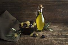 Olijfolie met olijven en tak op houten achtergrond stock foto