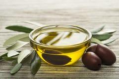 Olijfolie met zwarte olijven en bladeren Stock Foto