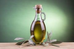 Olijfoliefles met groene schijnwerperachtergrond Royalty-vrije Stock Afbeeldingen