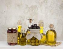 Olijfolieflessen en kruiken met vruchten op abstracte achtergrond royalty-vrije stock fotografie