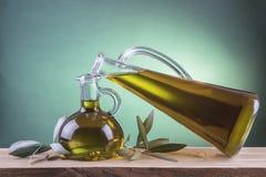 Olijfolieflessen op een groene schijnwerperachtergrond Royalty-vrije Stock Afbeelding