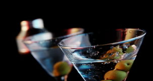 Olijfstok die in het cocktailglas vallen stock videobeelden