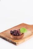 Olijven in een houten geïsoleerde plaat en een ruwe raad Stock Foto