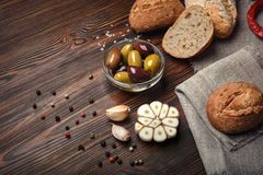 Olijven in olie met kruiden in glasvaas en brood op lijst stock afbeelding