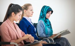 Olik affärskvinna som sitter, i möte inklusive asiatisk amerikan och islam royaltyfri fotografi