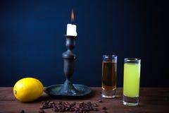 Olik drink två på en trätabell med en ljusstake tonat Arkivbilder