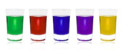 Olik färg dricker i exponeringsglas på vit bakgrund arkivbilder