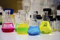 Olik färgrik lösning i konisk flaska på en bänk i en kemilabb med experiment för organisk kemi för suddighetsbakgrund arkivfoton