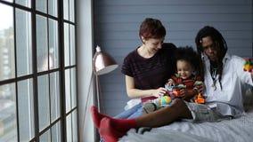 Olik familj med sonen som tillsammans hemma kopplar av arkivfilmer