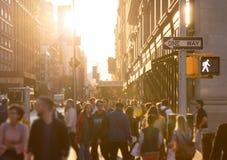 Olik folkmassa av anonymt folk som går ner en upptagen gata i New York City arkivfoto