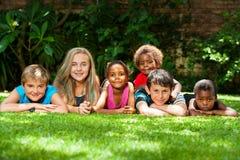 Olik grupp av ungar tillsammans i trädgård. Royaltyfri Bild