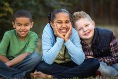 Olik grupp av ungar utanför på en parkera Royaltyfri Foto