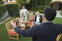 Olik grupp av vänner som firar med vin Arkivfoton
