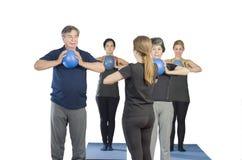 Olik grupp människor en idrottshallgrupp som gör den bollPilates övningen royaltyfria foton
