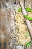 Olik hemlagad ny okokt italiensk pasta med mjöl, basilika arkivbild