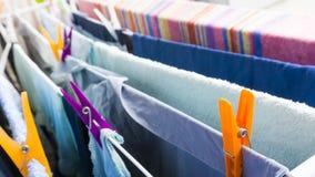 Olik kläder som hänger med färgrikt ben på clotheshorsen för att torka på balkongen royaltyfria foton