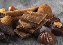 Olik konfekt: choklad godisar på en mörk bakgrund arkivbild