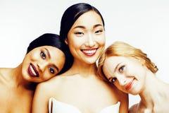 Olik kvinna för nation tre: asiat afrikansk amerikan, caucasian som isoleras tillsammans på lyckligt le för vit bakgrund fotografering för bildbyråer