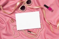 Olik kvinnatillbehör på rosa tyg Åtlöje upp för konstverk Royaltyfri Bild