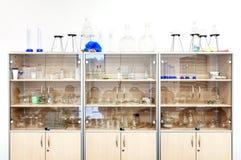Olik laboratoriumglasföremål och utrustning på hyllor Royaltyfria Foton