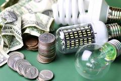 Olik lampor och pengarbunt på den isolerade gröna tabellen Arkivbilder