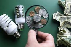Olik lampor och pengarbunt på den isolerade gröna tabellen Royaltyfri Fotografi