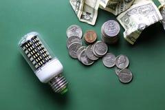 Olik lampor och pengarbunt på den isolerade gröna tabellen Arkivfoto