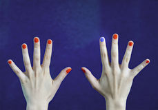Olik man spikar färg i finger i caucasian händer Röda och blåa målade fingernaglar arkivbild