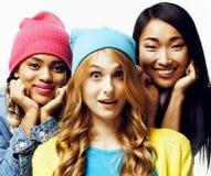 Olik nationflickagrupp, tonårs- gladlynt vänföretag ha gyckel, lyckligt le, gulligt posera som isoleras på vit arkivfoto