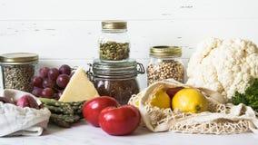 Olik ny mat - grönsaker och frukter i eco-vänskapsmatch packe på vit marmorerar bakgrund Vegetariskt sunt organiskt mål arkivfoto