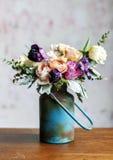 Olik ordning för nya blommor i metallisk vas på trätabl Arkivbilder