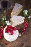 Olik ost med den vita och blåa formen Ett exponeringsglas av rött vin och nya bär för röd vinbär blommar white Träbakgrund och royaltyfri bild