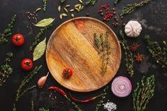 Olik smaktillsats för att laga mat på en mörk bakgrund Tom träplatta, kryddor, örter, grönsaker B?sta sikt, lekmanna- l?genhet arkivbild