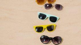 Olik solglasögon på strandsand stock video