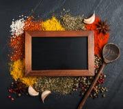 Olik sort av kryddor och svart tavla Royaltyfri Foto