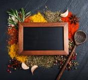 Olik sort av kryddor och svart tavla Arkivbilder