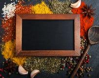 Olik sort av kryddor och svart tavla Arkivfoto